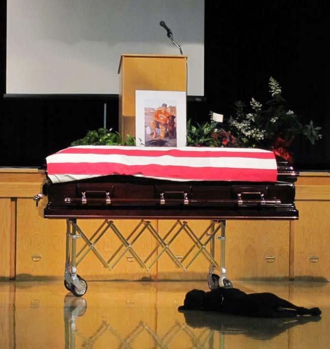 Hawkeye, labradorul retrivier negru care s-a aşezat lângă sicriul lui Jon Tumilson ce făcea parte din Forţele Navale Americane de-a lungul ceremoniei funerare din 2011